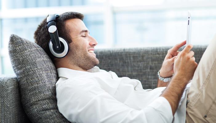man-on-sofa-listening-to-headphones